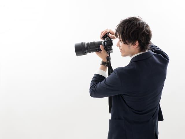 カメラを縦位置で構える男性